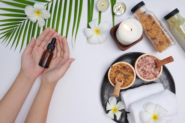 Le mani di una bella donna tengono una bottiglia di siero. olio essenziale di pino. trattamento termale e prodotto per spa mano femminile, massaggi e candele, relax. lay piatto. vista dall'alto.