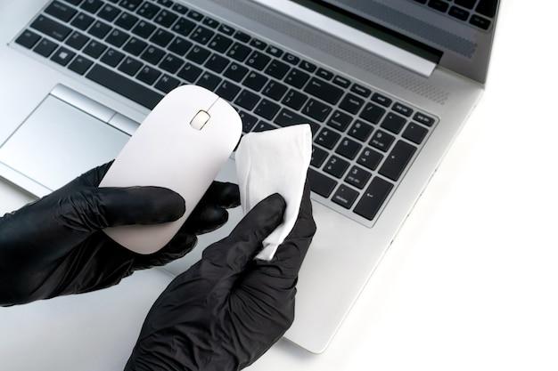 Mani in guanti neri pulire un mouse del computer con un panno umido antibatterico
