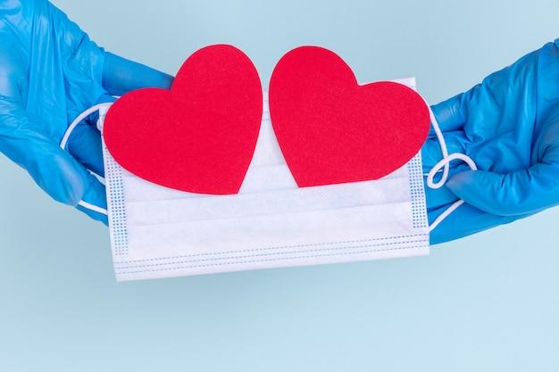 Le mani in guanti blu tengono una mascherina medica con due cuori rossi di amore di carta