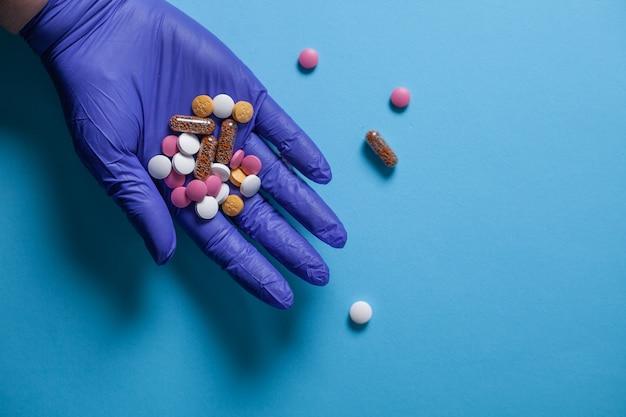 Le mani in guanti medici blu tengono una manciata di pillole su sfondo azzurro.