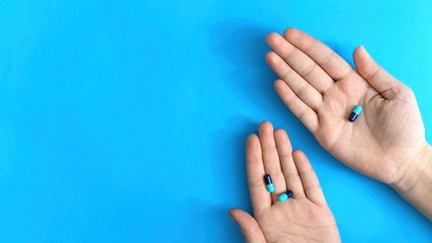 Mani pillole blu. sfondo blu. vista dall'alto