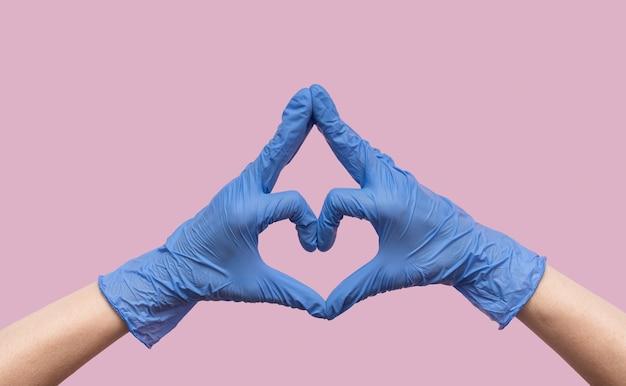 Mani in guanti medicali di gomma blu a forma di cuore su uno sfondo rosa.