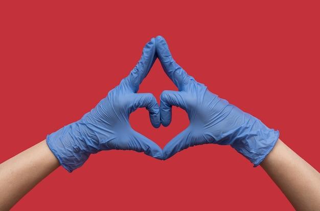 Mani in guanti protettivi medici in gomma blu a forma di cuore su uno sfondo rosso.