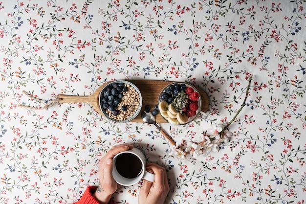 Le mani di un ragazzo con una tazza di caffè e yogurt con frutta su un letto