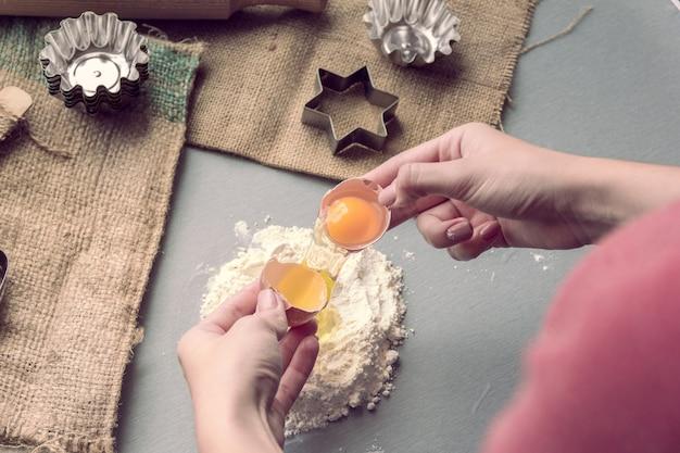 Le mani rompono un uovo di gallina in farina