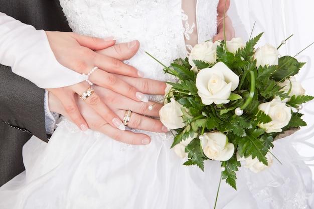 Mani degli sposi con anelli e bouquet da sposa