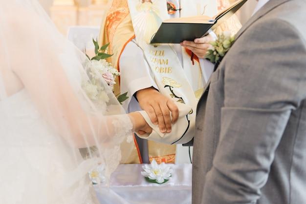 Mani della sposa e dello sposo e il primo piano del sacerdote. il sacramento del matrimonio nella chiesa