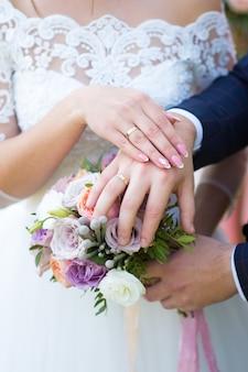 Mani della sposa e dello sposo sul bouquet da sposa