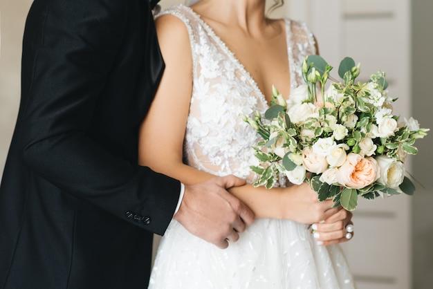 Mani della sposa e dello sposo con il primo piano dei mazzi