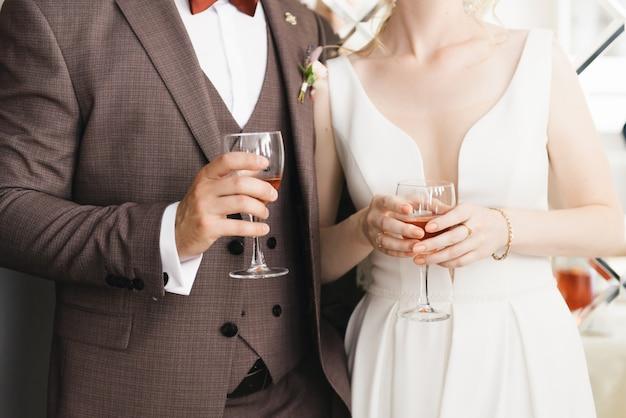 Le mani della sposa e dello sposo con i vetri si chiudono su