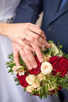 Mani della sposa e dello sposo con anelli sul bouquet da sposa. concetto di matrimonio ..