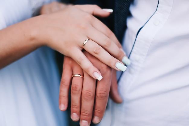 Mani della sposa e dello sposo con anelli. giorno delle nozze, sposa e sposo. dettagli del matrimonio