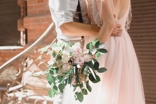 Mani della sposa e dello sposo con bouquet da sposa di fiori. fotografia d'arte.