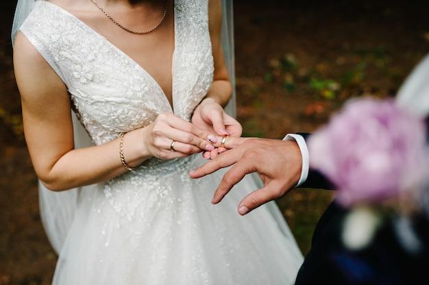 Le mani della sposa indossa un anello di fidanzamento nuziale al dito dello sposo. matrimonio in natura. gioielleria. avvicinamento. novelli sposi.