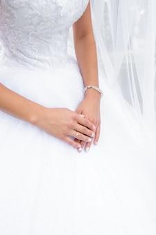 Mani della sposa con anello nuziale al dito sullo sfondo abito da sposa.
