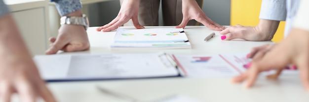 Mani di uomini d'affari al tavolo di lavoro con grafici commerciali. analisi aziendale e concetto di strategia di sviluppo aziendale