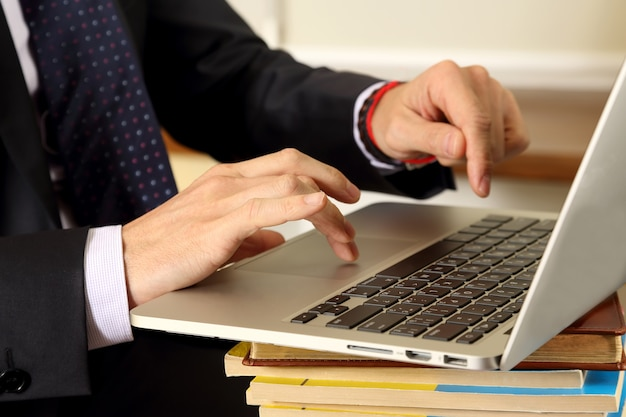 Mani di uomini d'affari che lavorano al computer portatile