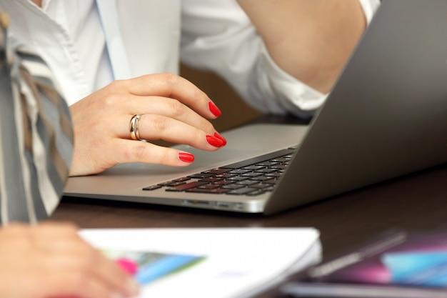 Mani della donna di affari che lavorano al computer portatile