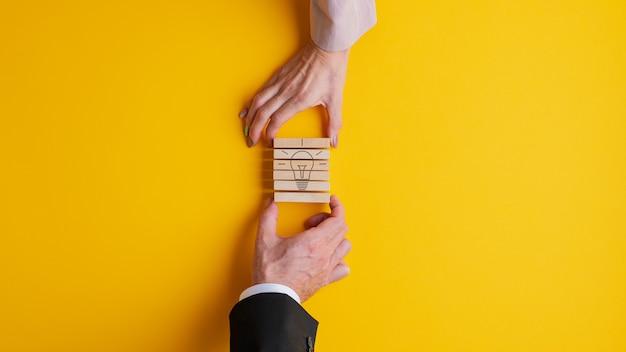 Mani di un uomo d'affari e di una donna di affari che impilano i pioli di legno per assemblare un'immagine della lampadina