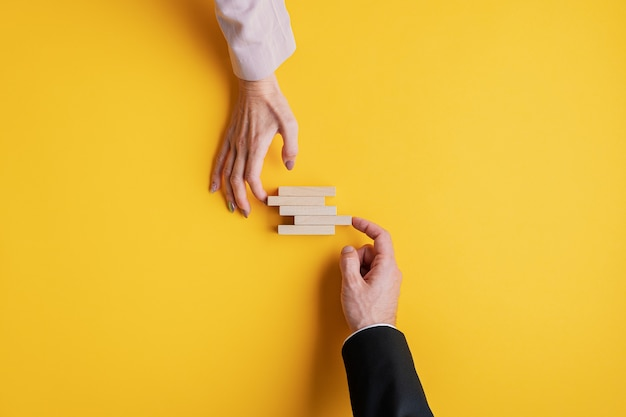 Mani di un uomo d'affari e di una donna d'affari che impilano pioli di legno in un'immagine concettuale di stabilità aziendale e lavoro di squadra.