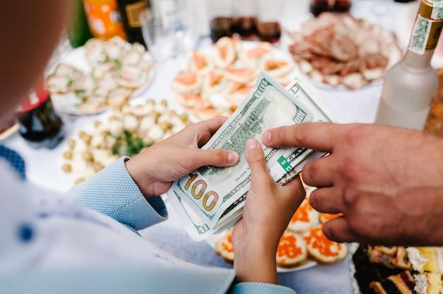 Le mani dell'uomo d'affari danno lo scambio di denaro alla donna d'affari, tenendo in mano un dollaro usa, usd. bollette, offre banconota in dollari. contanti nel concetto di affari, concussione e corruzione. pagare un risarcimento ai soci.