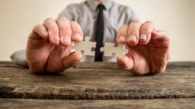 Mani di un uomo d'affari che tengono i pezzi di puzzle