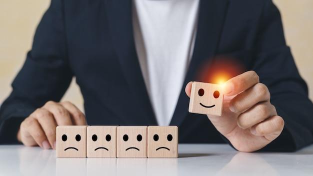 Le mani dell'uomo d'affari prendono i blocchi di cubo di legno di selezione con le icone di emozione del sorriso e l'emozione infelice non selezionata. valutazione e classificazione del concetto di business.
