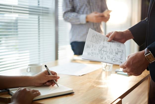 Mani dell'uomo d'affari che presentano la sua idea di sviluppo aziendale ai colleghi alla riunione
