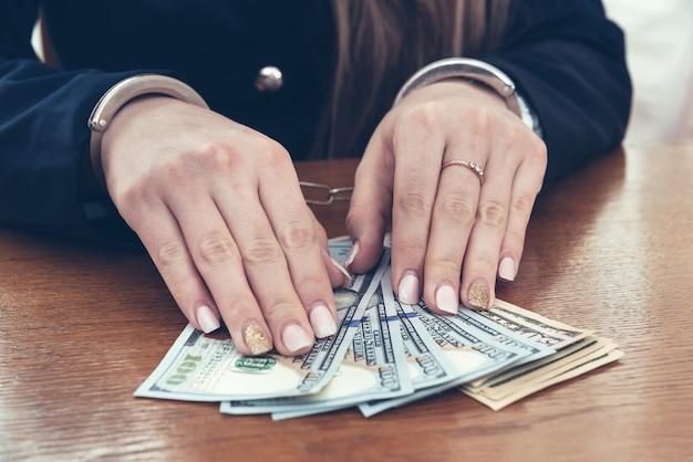 Mani di imprenditrice in manette con banconote in dollari