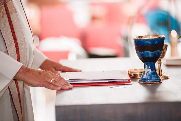Mani del sacerdote cattolico sull'altare con la lettura del calice dell'oro dal libro sacro