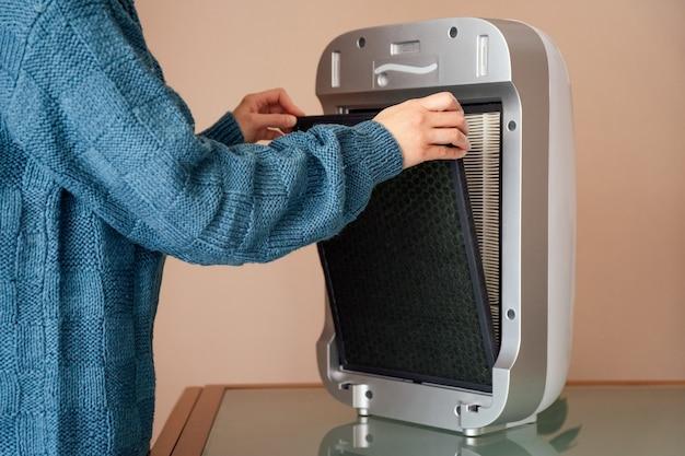 Mani che cambiano i filtri dell'aria, della polvere, del carbone e del depuratore di hepa