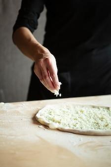 Le mani dello chef stanno preparando la pizza. versa il formaggio sulla pasta arrotolata