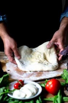 Mani dello chef chef italiano che cucina le mani dell'uomo della pizza che cucinano la pasta della pizza per pizza cuochi le mani
