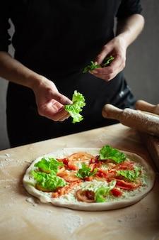 Mani dello chef che preparano la pizza. mettere gli ingredienti sulla pasta arrotolata