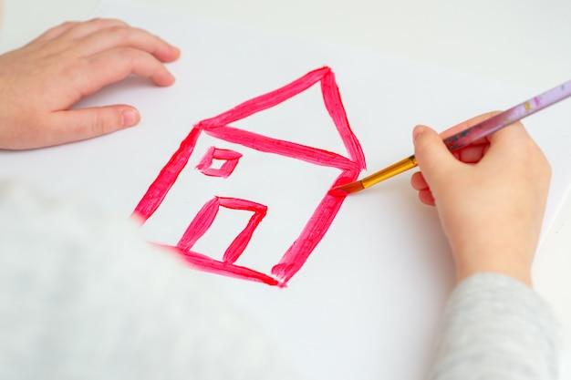 Mani del bambino che disegnano casa rossa