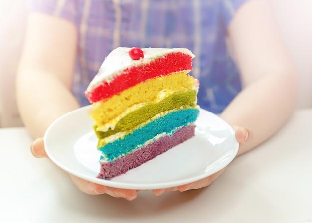 Mani di un bambino che tiene un pezzo di torta di compleanno. festa di compleanno