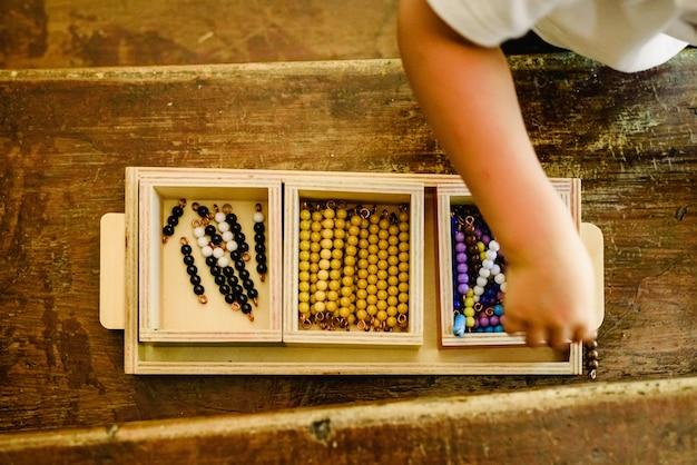 Mani di un bambino che manipolano materiali educativi per imparare a contare in una classe montessori.