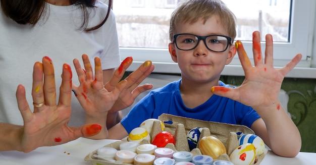 Le mani del bambino e del genitore sono macchiate di vernice quando decorano le uova per pasqua
