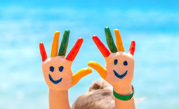 Sulle mani del bambino, un sorriso con i colori sul mare