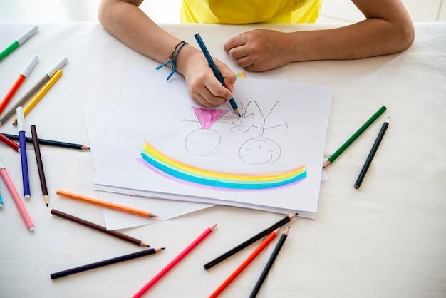 Mani di un bambino mentre disegna un concetto di padre di famiglia madre figlio genitori con matite