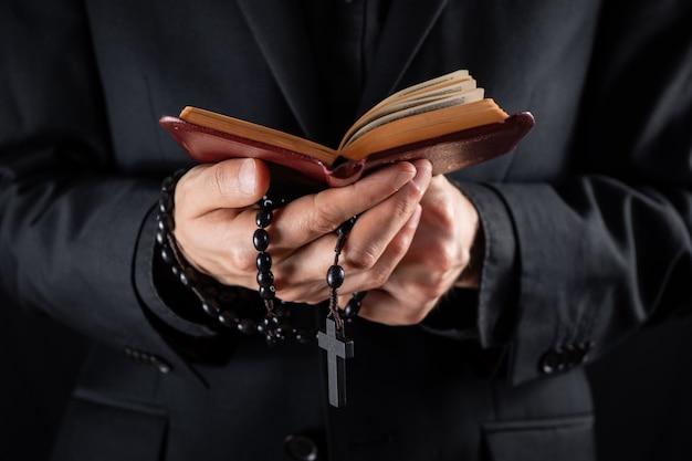 Le mani di un prete cristiano vestite di nero con in mano un crocifisso e la lettura del libro del nuovo testamento. la persona religiosa studia la bibbia e tiene perline di preghiera, immagine scura