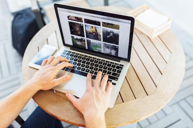 Le mani si chiudono su delle dita che scrivono sul computer portatile all'aperto