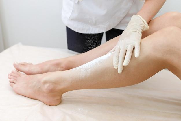 Il primo piano delle mani ha versato la polvere sui piedi del cliente. shugaring del piede