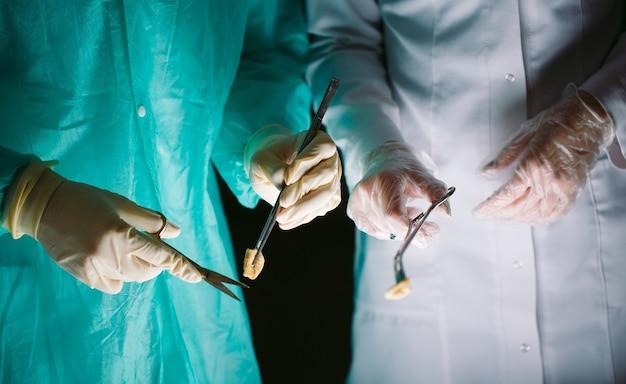 Primo piano delle mani dei chirurghi che tengono gli strumenti medici. il chirurgo fa un'operazione.