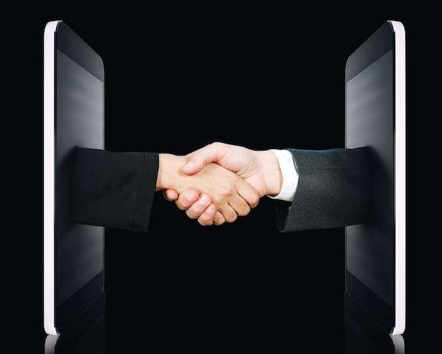Le mani escono dallo schermo per firmare un accordo o per conoscersi