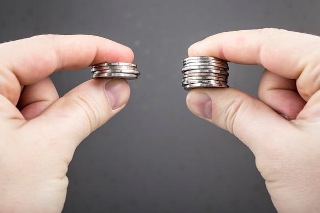 Le mani confrontano due pile di monete di diverse dimensioni
