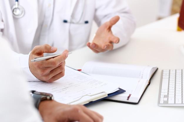 Le mani del medico interessato discutono il problema con il paziente maschio