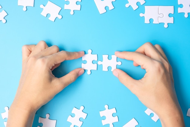 Mani che collegano i pezzi del puzzle di un paio di puzzle bianchi su sfondo blu. concetto di soluzioni, missione, successo, obiettivi, cooperazione, partnership, strategia e puzzle day