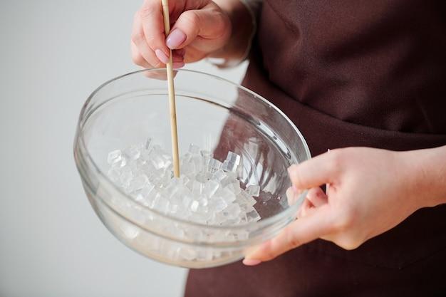 Mani di artigiana contemporanea che tiene la vetreria con cubetti di massa di sapone trasparente tagliata
