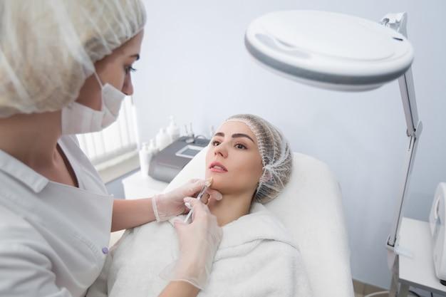 Mani del cosmetologo che fa iniezione in faccia, labbra